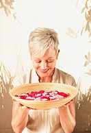 Middle_aged woman holding bowl of water and flower petals