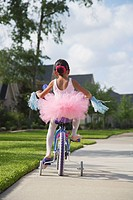 Girl in ballet outfit riding bicycle