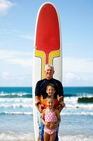 Grandfather and grandchildren in front of surfboard at beach