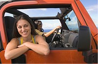 Hispanic woman leaning out window of jeep