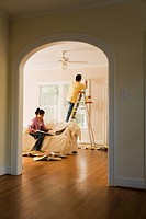 Hispanic couple painting new home