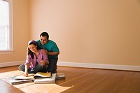 Hispanic couple looking at textile swatches in new home