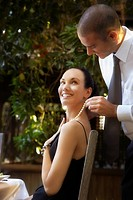Man putting necklace on woman at restaurant