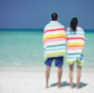 Couple wrapped in towels at beach