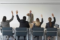 Businessman pointing at co_workers with hands raised