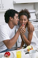 African man feeding fruit to girlfriend
