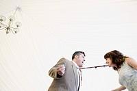 Hispanic woman biting husband´s tie