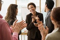Multi_ethnic businesspeople clapping for coworker