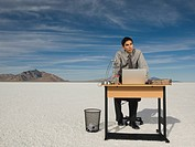 Hispanic businessman at desk on salt flats