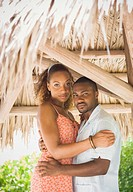 African American couple hugging in grass hut