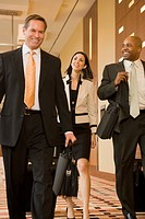 Multi-ethnic business people walking with suitcases down corridor (thumbnail)