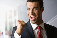 Smiling Hispanic businessman raising fist