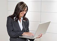 Hispanic businesswoman holding laptop