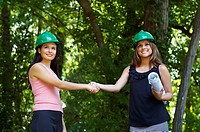 Hispanic architects in green hard hats shaking hands outdoors