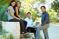 Hispanic business people using laptop outdoors