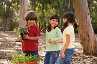 Hispanic children holding potted trees