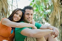 Hispanic couple hugging in tropical area