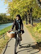 Mature woman cycling along river