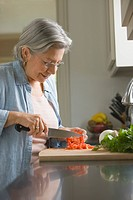 Senior Hispanic woman chopping fresh vegetables