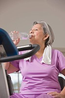 Senior Hispanic woman drinking water after workout