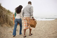 Couple walking on beach with picnic basket