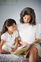 Hispanic grandmother reading to granddaughter in bedroom
