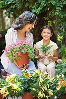Hispanic grandmother and granddaughter holding plants in garden