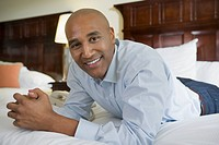 African businessman on hotel bed smiling