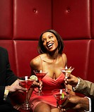 Men offering glamorous African woman cocktails