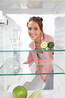 Portrait of young woman smiling in front of open refrigerator