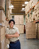 Male warehouse worker leaning on boxes