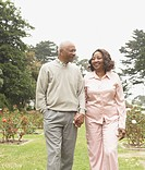 Senior African couple holding hands and walking outdoors