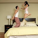 Asian couple jumping on bed