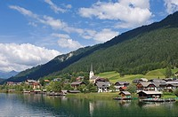 Houses and church at lakeside, Weissensee, Techendorf, Carinthia, Austria