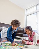 African American siblings playing board game