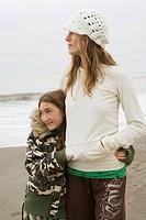 Mixed race woman and sister hugging at beach