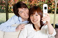Yuong couple taking a photo by mobile