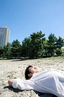 Young man lying on the sand