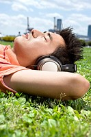 Young man with headphone lying on the grass