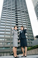 Two business women in front of the building