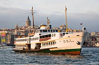 Boat crossing the Bosphorous with the Galata Tower in background Karaköy district Golden Horn Istanbul Turkey