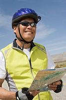 Senior man in sportswear reading map