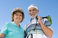 Senior couple holding tennis equipment portrait