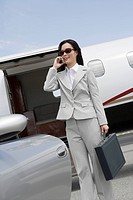 Mid_adult businesswoman using mobile phone in front of airplane and car.
