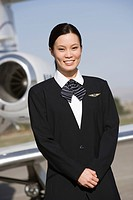 Portrait of Asian mid_adult flight attendant in front of airplane.