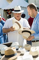 Men shopping hats during ´Feria de la Pentecôte´, Nîmes. Gard, Languedoc-Roussillon, France