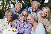 Senior people celebrating birthday in garden smiling