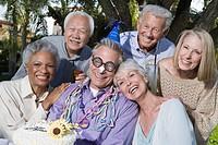 Senior people celebrating birthday in garden smiling