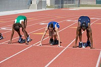Female athletes in starting blocks ready to run