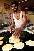 A man cooking traditional Dosas at a restaurant in Kanyakumari Cape Comorin, Tamil Nadu, India